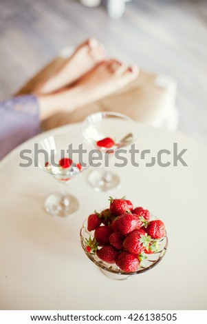 legs near strawberry and drinks - stock photo