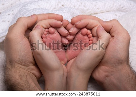 Legs newborn baby hands hug mom and dad, forming a heart. Symbolizes love, unity, caring, tender to the baby - stock photo