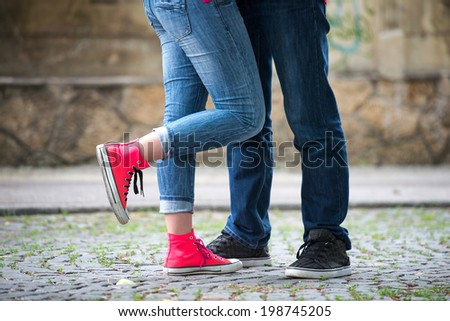Legs of a couple of teenagers in love - stock photo