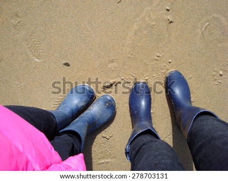 legs of a little girl and a young woman standing on a Cornwall beach in blue boots                                - stock photo