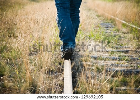Legs of a lonely man walking on a rail on a disused railway line.