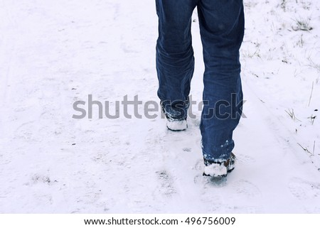 Legs of a person who goes on early newly fallen snow.