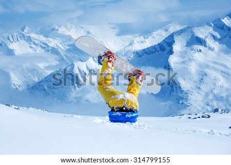 Legs of a snowboarder stuck in deep snow upside down - stock photo