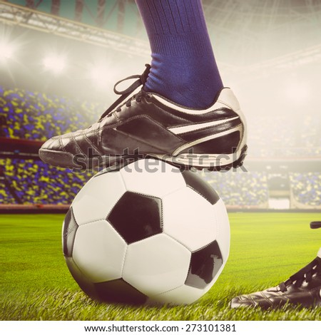 legs of a soccer or football player on ball on stadium, warm colors toned - stock photo