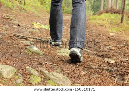 Legs of a woman in boots hiking on the mountain path