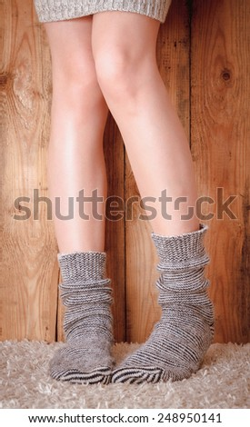 Legs of a woman in gray socks and gray sweater on the carpet on the wooden background - stock photo
