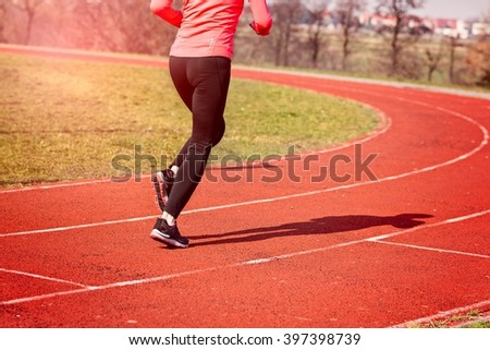 Legs of a woman running around the track on a sunny spring day. Woman running concept. Runner jogging training workout