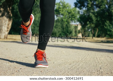 Legs of a woman running on a dirt road - stock photo