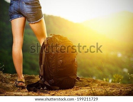 legs of a woman tourist and travel backpack on a mountain top at sunset - stock photo