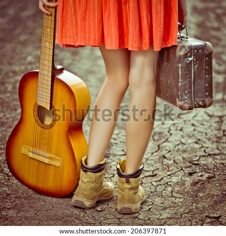 legs of a woman tourist with suitcase and guitar standing on rural road. toned vintage image - stock photo