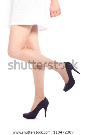 Legs of a woman with high heels on white background with left leg raised - stock photo