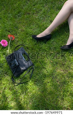 Legs of a women resting on green grass a lot of copyspace
