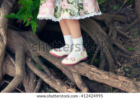 Legs of a young child standing on a branch of a big tree - stock photo