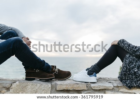 Legs of a young couple with lights in the evening by the sea - stock photo