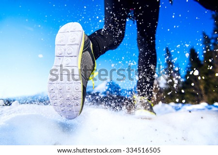 Legs of a young runner outside in winter nature - stock photo