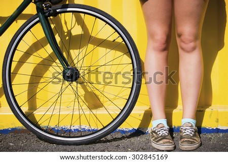 legs of a young woman near bicycle wheel on a yellow background selective focus - stock photo