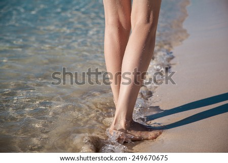 Legs of a young woman walking along the seacoast