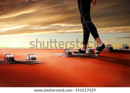 Legs of athlete on start line of running track on sunset background - stock photo