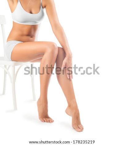 legs of beautiful female sitting on chair - stock photo