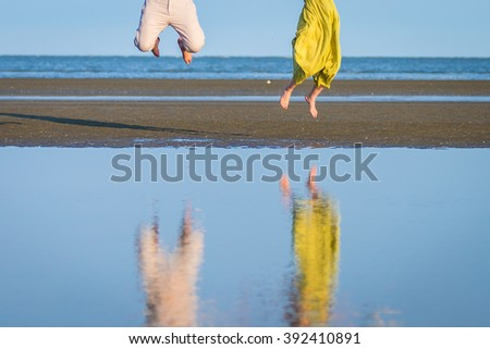 Legs of couple in love while jumping on beach with reflection from water, romantic vacation