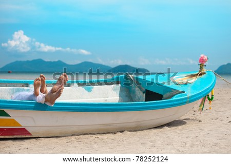 legs of couple in the boat on the beach - stock photo