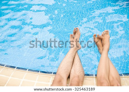 Legs of couple sitting on the poolside