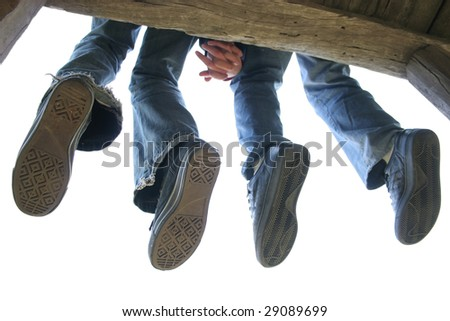 Legs of Couple sitting on the wooden bench - stock photo