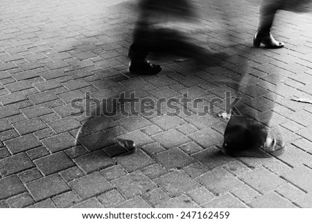 Legs of different people walking on the sidewalk tile on the street. Minsk, Belarus, black and white image. Motion Blur