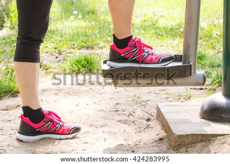 Legs of elderly senior woman in sports shoes exercising on outdoor gym in sunny park, trainer machine, healthy, sporty lifestyles and slimming concept