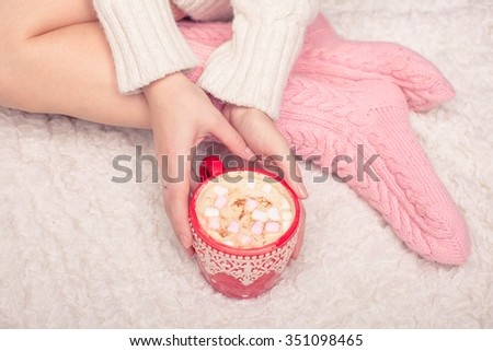 legs of girl in warm woolen socks and a cup of coffee warming, winter morning at home - stock photo