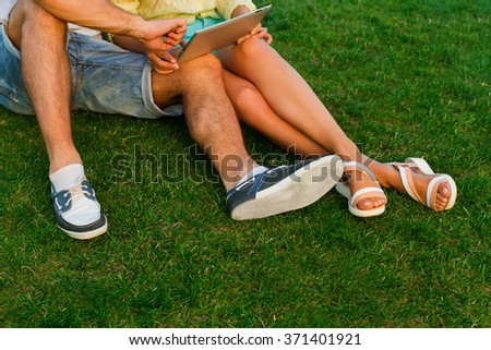 Legs of in love couple relaxing in the park. Guy and girl play games on the tablet. Communication on the Internet in the park. A date of lovers on the nature.