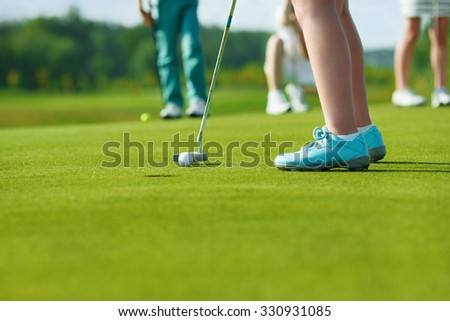 Legs of kids playing golf and hitting by putter on green - stock photo