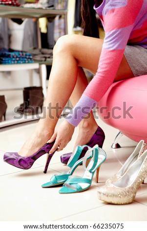 Legs of lady trying on several pairs of new shoes in the mall