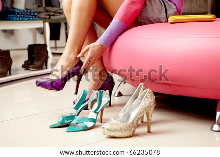 Legs of lady trying on several pairs of new shoes in the mall - stock photo