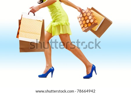 Legs of lady with colorful paper bags in move - stock photo