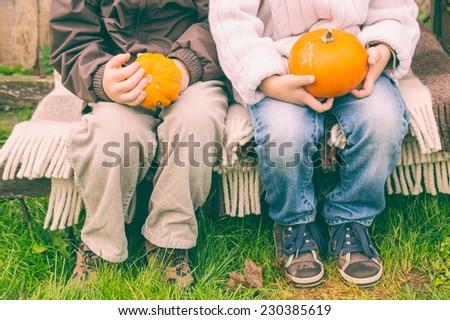 Legs of little friends sitting on cart with pumpkin - stock photo
