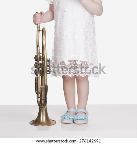 legs of little girl in blue shoes.musical child.little girl with trumpet.musical instrument - stock photo