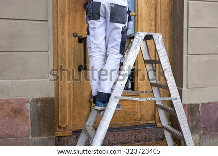 Legs of man in white stained overalls on metal stepladder - stock photo