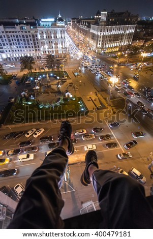 Legs of man sititng on roof above street in center of Moscow at night