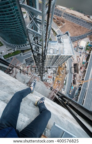 Legs of man sitting on roof of tall building on construction site in Moscow - stock photo