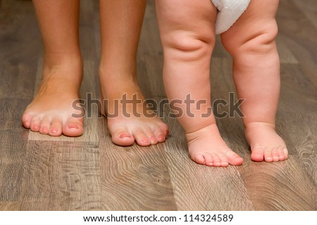 Legs of mother and baby. First steps. - stock photo