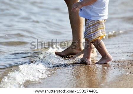 Legs of mother and child when they entering into the sea