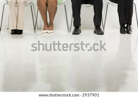 Legs of multi-ethnic business group of men and women sitting.