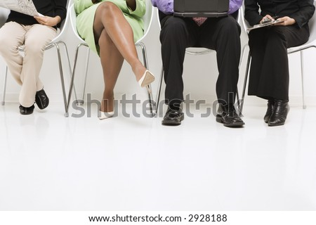 Legs of multi-ethnic business group of men and women sitting with laptop and papers.