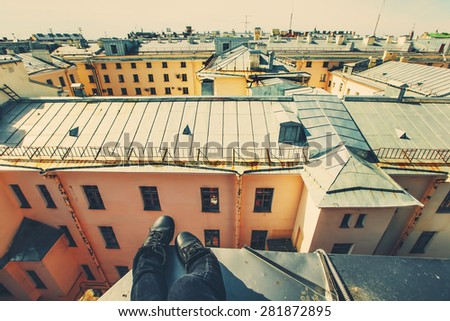Legs of person sitting on the roof top with skyline city views
