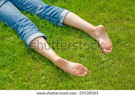 Legs of relaxing woman in green grass