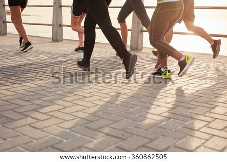 Legs of runners training together on seaside promenade. People running on the street by the sea.