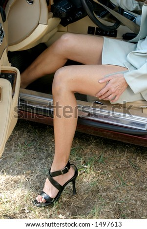 Legs of sexy, attractive brunette woman getting out or getting in an elegant luxury car. - stock photo