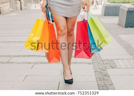 Legs of shopaholic wearing dress while carrying several paperbags