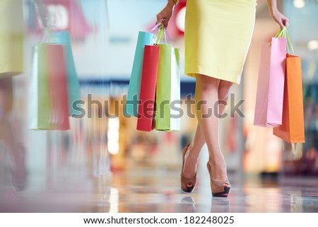 Legs of shopaholic with shopping bags walking down mall - stock photo